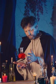 Ritratto di mago con candele accese e pozioni magiche