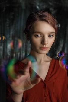 Ritratto di magro giovane ragazza caucasica in camicia rossa. bolle di sapone volano intorno alla sua testa scintillante di colori arcobaleno.