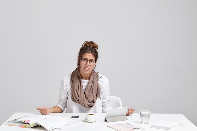 Ritratto di malcontento stanco giovane bella imprenditrice si siede alla scrivania in ufficio