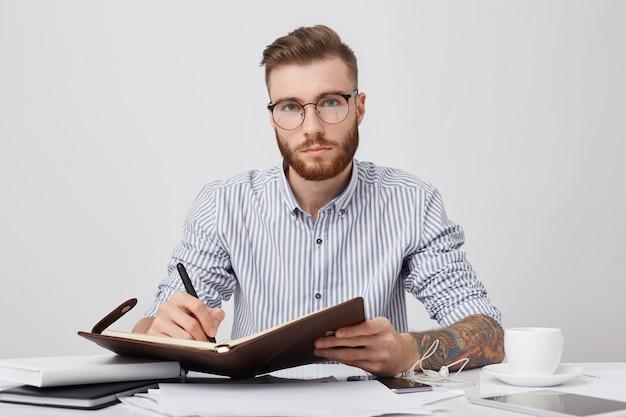 Ritratto di manager maschio fiducioso con tatuaggi, scrive nel piano di diario per la prossima settimana, beve caffè