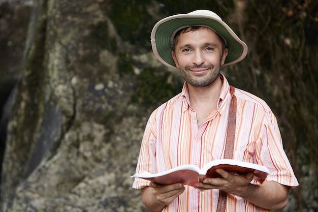 Ritratto di maschio botanico o biologo con stoppie che indossa cappello panama e maglietta a righe al lavoro sul campo, tenendo il taccuino nelle sue mani con espressione felice e allegra