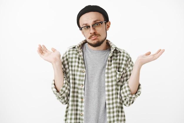Ritratto di maschio incerto cupo ignaro incerto con la barba in camicia a quadri casual e berretto nero che stringe le labbra che scrolla le spalle e allarga le mani da parte in un gesto incapace