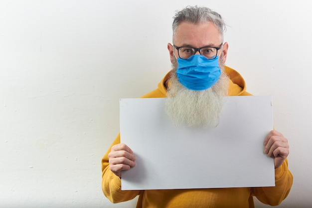 Ritratto di maturo uomo barbuto dai capelli grigi in maschera protettiva medica con foglio bianco