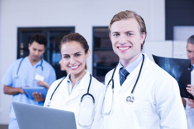 Ritratto di medici che per mezzo del computer portatile e sorridendo mentre i suoi colleghi che discutono dietro
