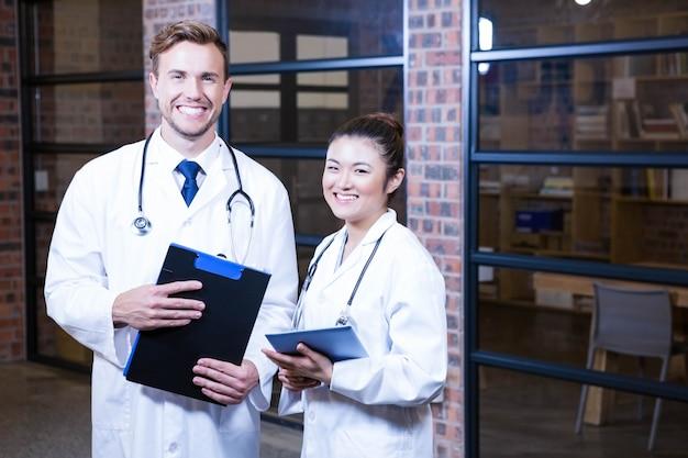 Ritratto di medici che stanno biblioteca vicina con la lavagna per appunti e la compressa digitale in ospedale