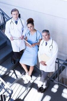 Ritratto di medici che stanno sulla scala con il documento in ospedale