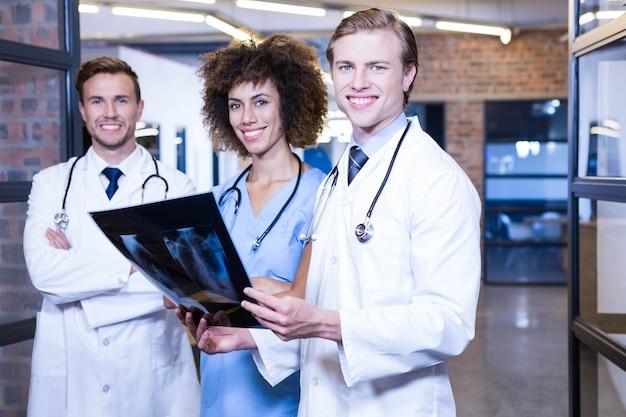 Ritratto di medici con il rapporto dei raggi x in ospedale