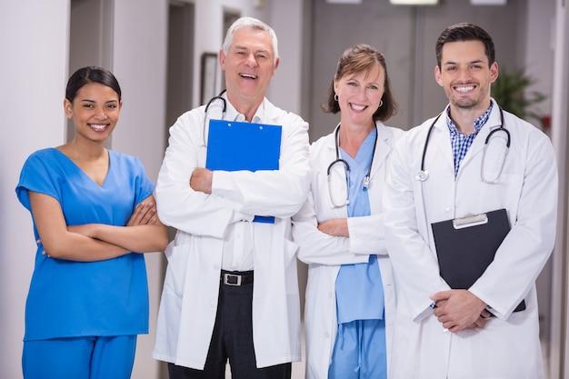 Ritratto di medici e infermiere sorridenti che stanno con le armi attraversate