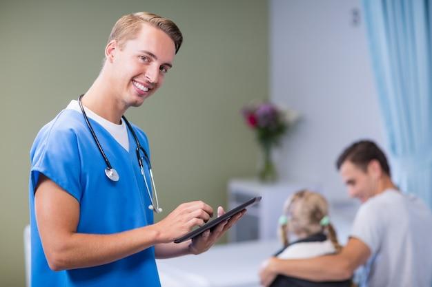Ritratto di medico che per mezzo della compressa digitale