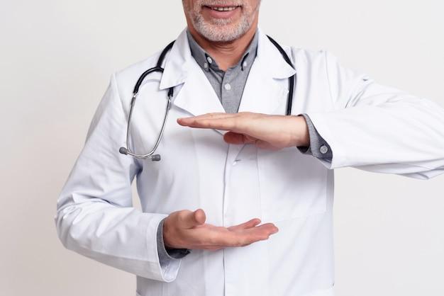 Ritratto di medico con lo stetoscopio che si tiene per mano isolato.