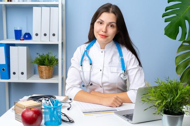 Ritratto di medico della donna alla sua scrivania, interno dell'ufficio