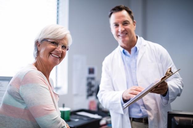 Ritratto di medico e paziente senior che discutono sulla lavagna per appunti