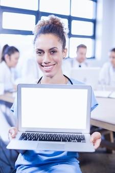 Ritratto di medico femminile che mostra computer portatile e altri medici che discutono dietro nell'auditorium