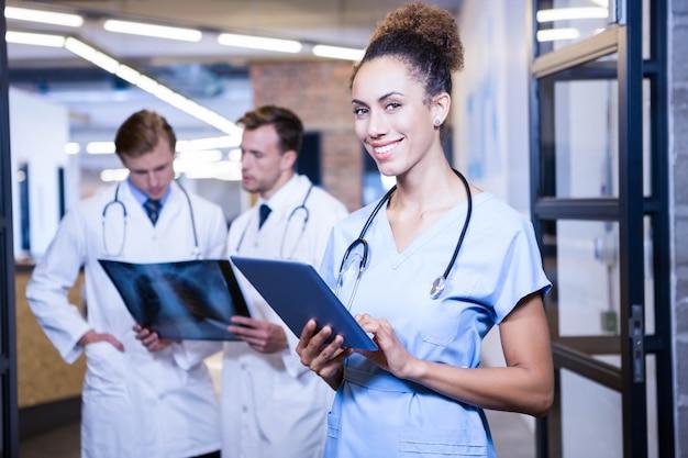Ritratto di medico femminile con la compressa digitale in ospedale e colleghi che stanno dietro e che discutono