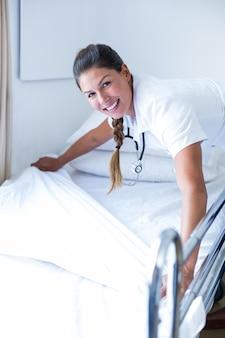 Ritratto di medico femminile sorridente che prepara il letto