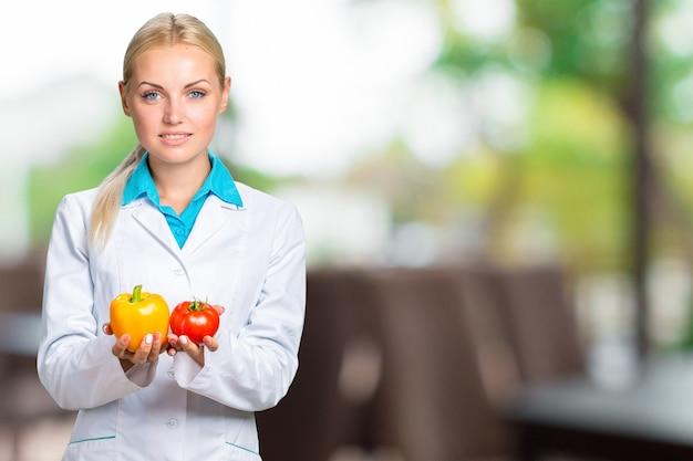 Ritratto di medico femminile sorridente in abito bianco che giudica gli ortaggi freschi isolati