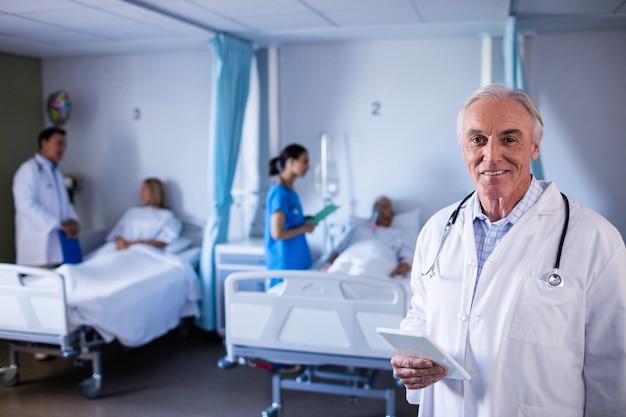 Ritratto di medico maschio che sorride mentre tenendo compressa digitale