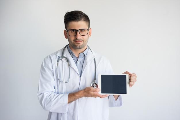 Ritratto di medico maschio sicuro che mostra compressa digitale.