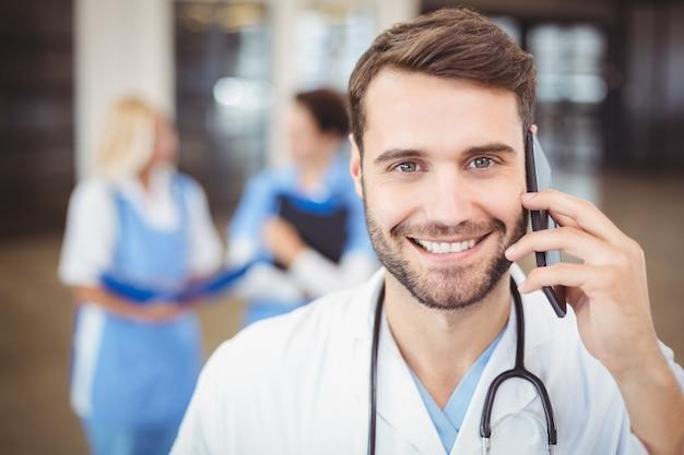 Ritratto di medico sorridente che parla sul telefono cellulare