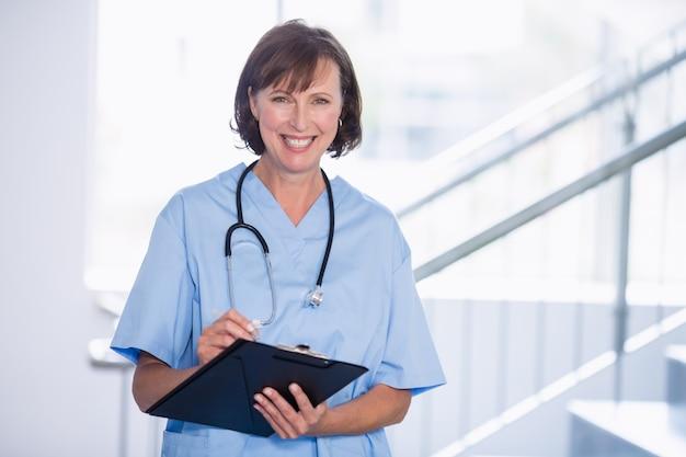 Ritratto di medico sorridente che scrive sulla lavagna per appunti in corridoio