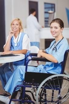 Ritratto di medico sorridente seduto sulla sedia a rotelle con i colleghi