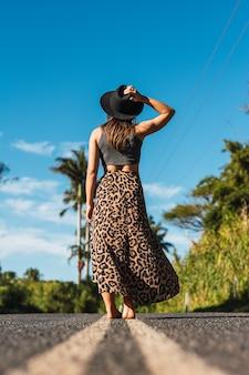 Ritratto di meraviglioso modello femminile bianco con cappello mentre si cammina sulla strada