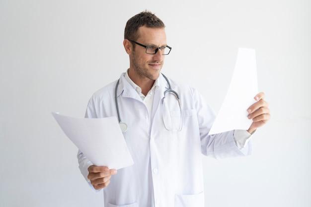 Ritratto di metà di medico adulto fiducioso guardando i documenti.
