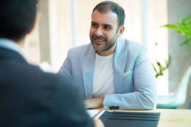 Ritratto di metà di uomo d'affari adulto sorridente che si siede nell'ufficio