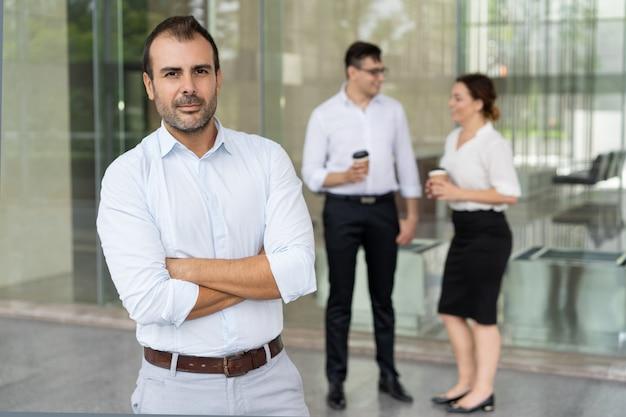 Ritratto di metà leader fiducioso adulto in piedi con le braccia conserte