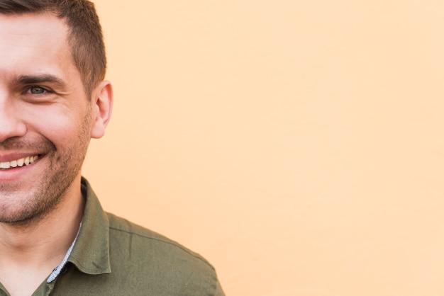 Ritratto di metà viso di giovane uomo di stoppie su sfondo beige