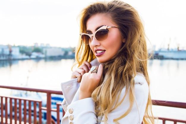 Ritratto di moda all'aperto di bella donna sensuale seducente che posa al porto marittimo nella luce del sole di sera, indossando occhiali da sole dorati di lusso alla moda e cappotto di cashmere.