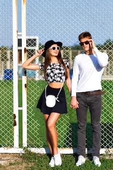 Ritratto di moda all'aperto di coppia innamorata abbracci al campo sportivo, vestiti alla moda in bianco e nero, occhiali da sole vintage, in posa a un appuntamento romantico, giornata di sole, colori vivaci, amore, relazioni.