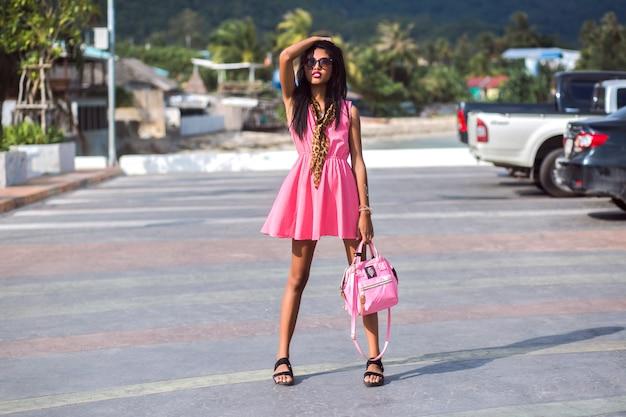Ritratto di moda all'aperto di donna tailandese asiatica piuttosto sottile in posa per strada, indossando mini abito rosa, sandali, occhiali da sole e borsa abbinata ai colori, umore di viaggio.