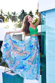 Ritratto di moda all'aperto di estate di splendida donna bruna con i capelli lunghi e trucco luminoso
