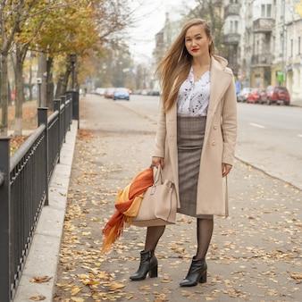 Ritratto di moda all'aperto di giovane bella donna alla moda che indossa trench lungo beige alla moda