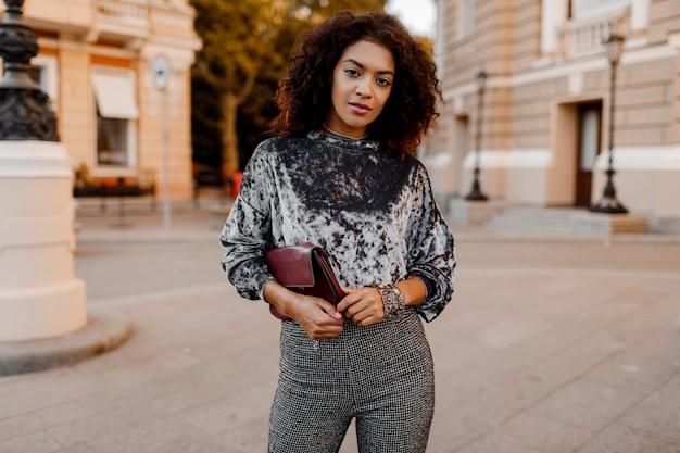 Ritratto di moda all'aperto di glamour sensuale giovane elegante signora nera che indossa un vestito alla moda autunno, maglione di velluto grigio e borsa di lusso.