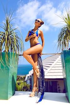 Ritratto di moda all'aperto di signora glamour che si gode la sua vacanza in villa di lusso nella calda isola tropicale, indossando occhiali da sole alla moda e bikini blu scuro. corpo abbronzato perfetto e gambe lunghe.