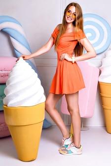 Ritratto di moda divertente di donna abbastanza bionda che tiene un gelato gigante, in posa vicino a grande dolcezza falsa, colori pastello, bel vestito, negozio di caramelle.