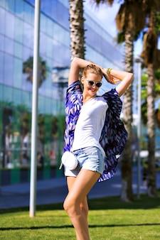 Ritratto di moda estiva all'aperto di donna alla moda in posa vicino a palme, godersi una vacanza esotica, abbigliamento casual, stivali e occhiali da sole, colori vivaci, viaggiare a barcellona, colori vivaci, street style.
