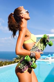 Ritratto di moda glamour di splendida donna sexy con corpo perfetto in forma che tiene skateboard luminoso, in posa vicino a vila di lusso con piscina e vista sull'isola esotica dell'oceano.
