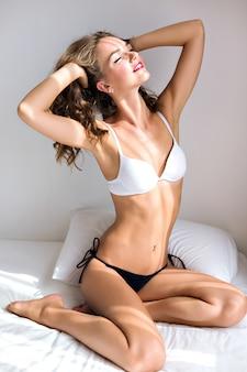 Ritratto di moda indoor lifestyle di donna con un corpo sexy slim fit incredibile, in posa sul letto al mattino, indossando lingerie casual semplice, rilassati e goditi la giornata di sole.