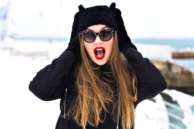 Ritratto di moda invernale di donna bionda sensuale, labbra carnose rosse, molta neve, cappello divertente, cappotto elegante, spedizione di viaggio invernale, capelli lunghi, tempo ventoso, incredibile mare ghiacciato.