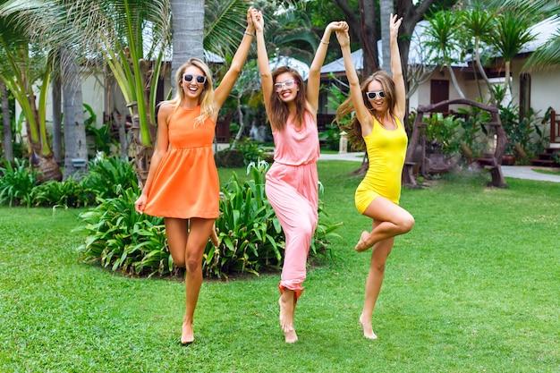 Ritratto di moda stile di vita all'aperto degli amici di belle ragazze che si divertono in vacanza, indossando eleganti abiti al neon luminosi e occhiali da sole. saltando e ballando al giardino tropicale.