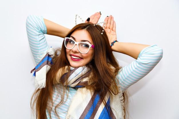 Ritratto di moda stile di vita carino di giovane donna graziosa bruna con capelli lunghi incredibili, trucco fresco e luminoso, divertirsi e gong pazzo, orario invernale, gattino imitato, orecchie da festa divertenti.