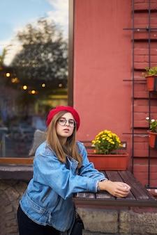 Ritratto di moda stile di vita soleggiato estate di giovane donna alla moda hipster che cammina sulla strada, indossando un vestito alla moda carino con cappello rosso