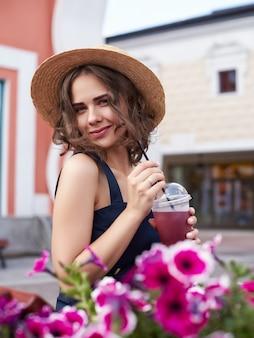 Ritratto di moda stile di vita soleggiato estivo di giovane donna alla moda hipster che cammina sulla strada, indossando un vestito alla moda carino,