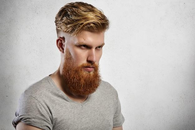 Ritratto di modello coraggioso con lunga barba sfocata e taglio di capelli alla moda in posa all'interno.