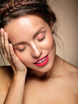 Ritratto di modello di bella donna con trucco quotidiano fresco e labbra rosse che toccano la sua testa