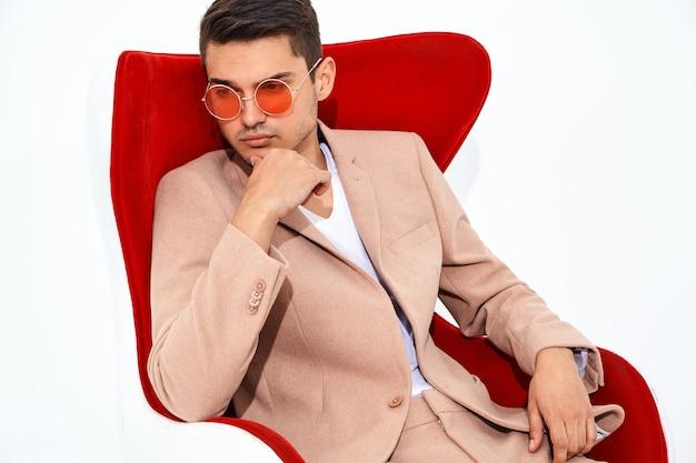 Ritratto di modello di uomo d'affari elegante moda bello vestito in elegante abito rosa chiaro seduto sulla sedia rossa. metrosexual