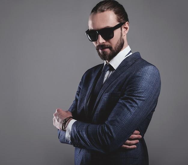 Ritratto di modello di uomo d'affari moda bello vestito in elegante abito blu con occhiali da sole
